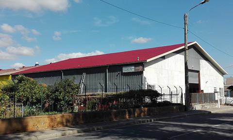 bâtiment en taule grise avec toiture neuve en taule rouge