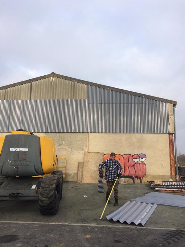 batiment industriel en beton avec tracteur et artisans